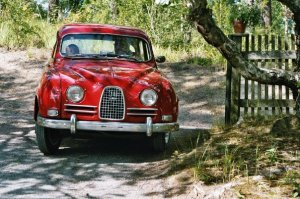Symboliikka kerrakseen - kotipihan portti, kiipeilykoivu, punainen isän kunnostama vanha Saab, ratissa Patu-isä ja kyydissä kurkkii Daniel