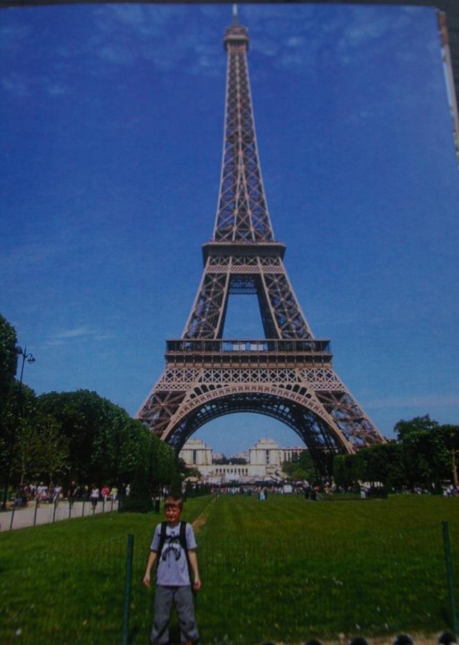 10 -vuotias Daniel poiksa seisoo Eiffel-tornin edessä Pariisissa